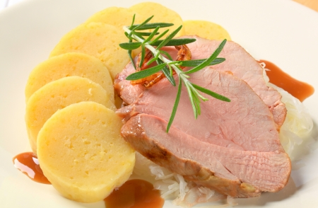 Dish of pork meat with potato dumplings and white cabbage photo