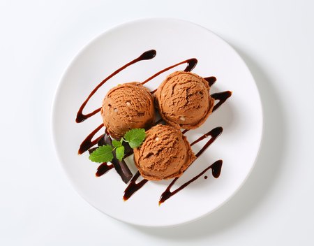 topping: Scoops of brown ice cream with chocolate syrup