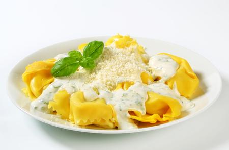 Špenát a ricotta plněné těstoviny podávané s bílým smetanovou omáčkou a strouhaným Parmigiano