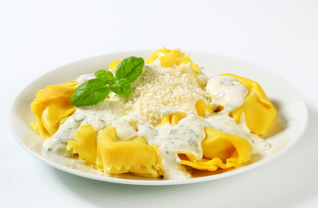 Spinach and ricotta stuffed pasta served with white cream sauce and grated Parmigiano photo
