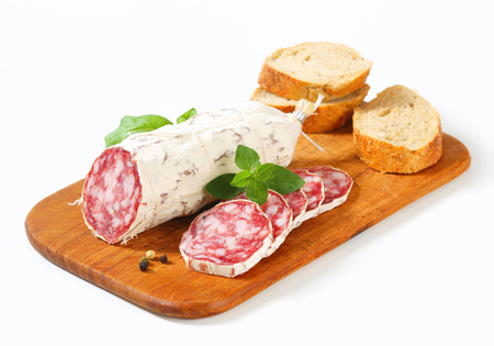 antipasto: French Saucisson Sec and sliced crispy roll on cutting board