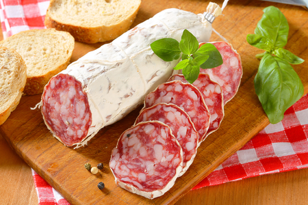 French Saucisson Sec and sliced crispy roll on cutting board photo