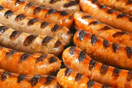 Grilled bratwursts on barbecue grid photo