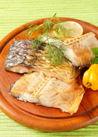 ovenbaked: Oven-baked carp fillets on round cutting board Stock Photo