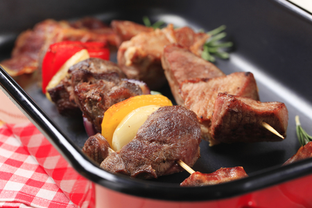 roasting pan: Shish kebabs and rashers of bacon in a roasting pan