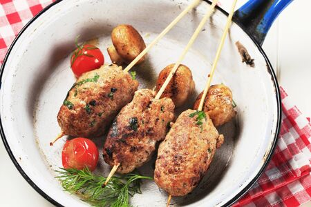 Minced meat kebabs and mushrooms in a pan photo