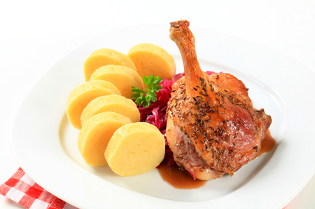 Dish of roast duck leg with potato dumplings and red cabbage photo