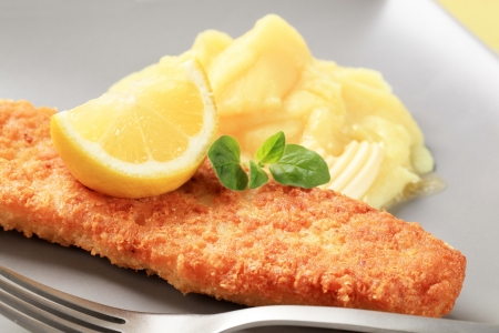 Fried battered fish fillet with potato puree and lemon