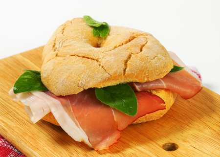 Ring-shaped bread roll (friselle) with slices of dry-cured ham photo