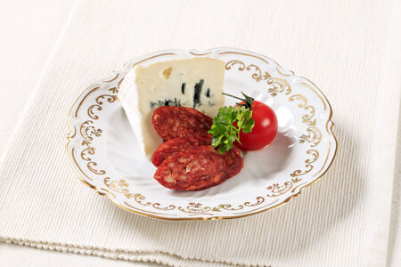 Blue cheese and slices of spicy sausage photo