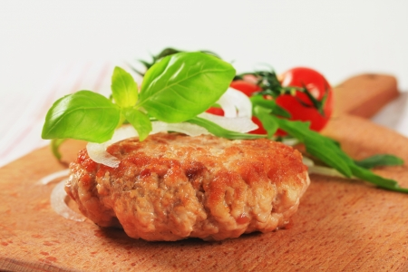 Pan fried meat patty on a cutting board photo