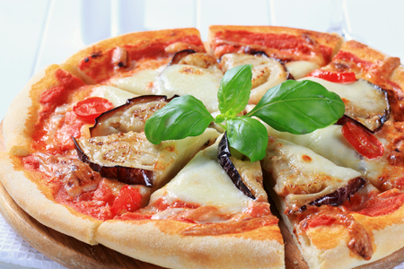 Pizza topped with cheese and slices of eggplant  photo
