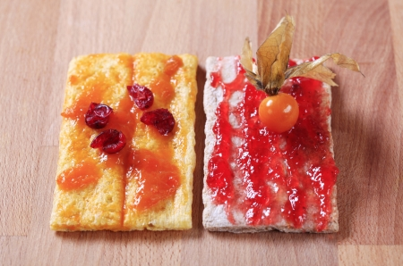 crispbread: Two slices of crispbread with strawberry and apricot preserves Stock Photo