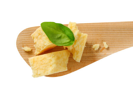 Pieces of Parmesan cheese on wooden spatula photo