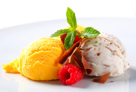Scoops of ice cream with chocolate curls and fruit photo