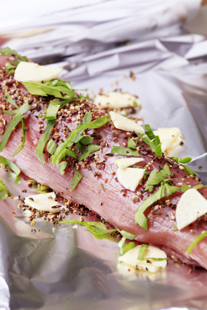Raw pork tenderloin seasoned with spices and garlic photo