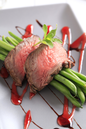 Slices of roast beef with string beans photo