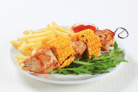 Turkey and sweetcorn skewer with French friesand ketchup photo