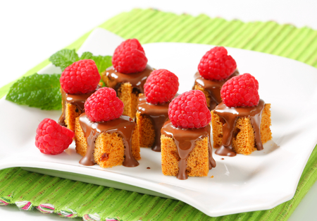 Bite-sized gingerbread squares with liquid chocolate and fresh raspberry on top photo