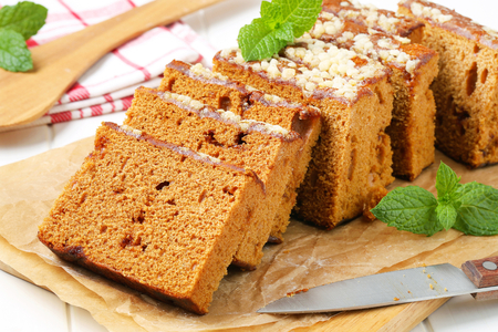 honey cake: Sliced gingerbread loaf on cutting board Stock Photo