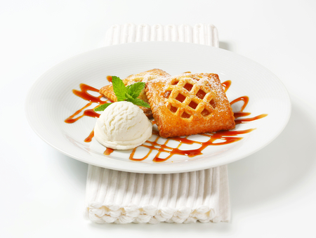 Little apricot pies with ice cream and drizzle sauce photo