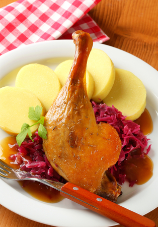 Dish of roast duck leg with potato dumplings and braised red cabbage photo
