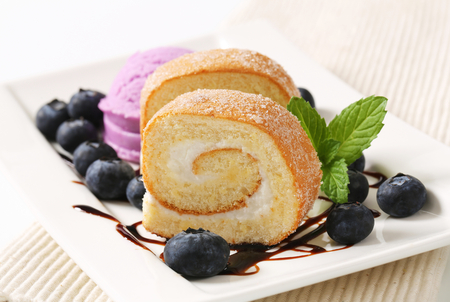 Sponge cake roll with ice cream and blueberries photo