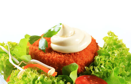 Green salad with fried breaded cheese and mayonnaise photo