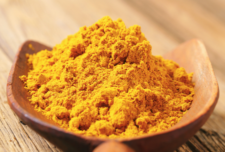 wooden scoop: Heap of curry powder on a wooden scoop