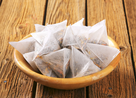 sachets: Pyramid-shaped jasmine tea bags in wooden bowl Stock Photo