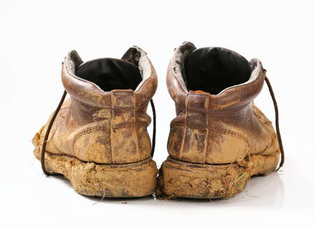 muddy clothes: Pair of dirty brown walking boots  Stock Photo