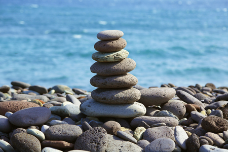 wellbeeing: Pyramid from pebbles against the sea