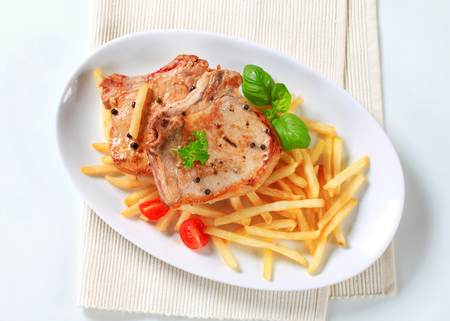 seared: Pan seared pork chop with French fries Stock Photo