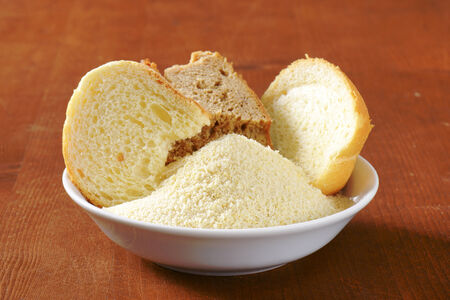 stale: Pieces of stale bread and pile of finely ground bread crumbs