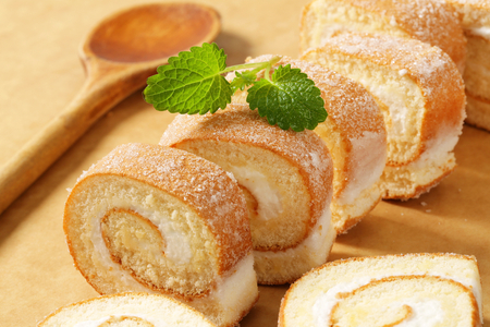 Slices of sponge cake roll with cream filling photo
