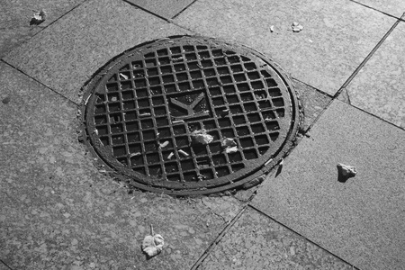 lurid: Infrared shot of round metal manhole cover on tiled pavement Stock Photo