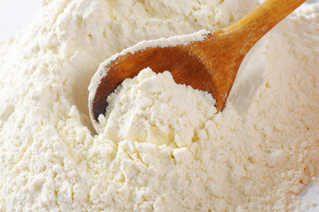 Pile of finely ground flour and wooden spoon