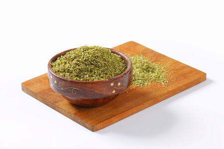 origanum: Heap of dried Marjoram leaves in a wooden bowl