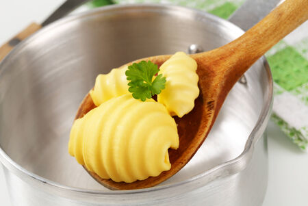 Butter curls on wooden spoon and saucepan photo