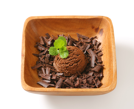 chocolate shavings: Scoop of ice cream and chocolate shavings in wooden bowl