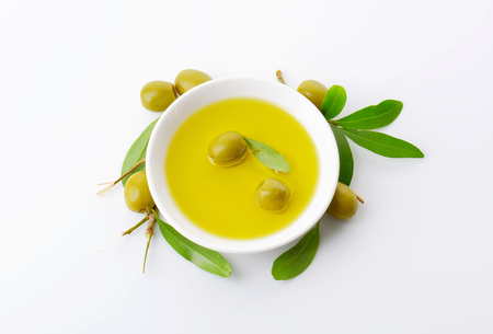 cooking oil: Pitted green olives and bowl of oil