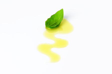 drizzle: Olive oil drizzle and fresh basil leaf Stock Photo