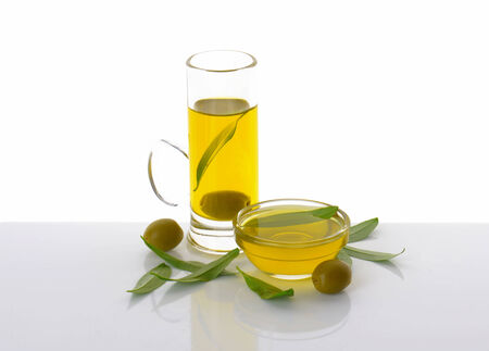 tall glass: Olive oil in tall glass mug and bowl Stock Photo