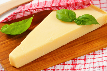 wedge: Wedge of Parmesan cheese on cutting board
