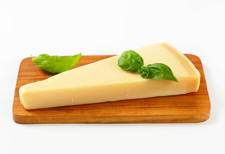 Parmesan: Wedge of Parmesan cheese on cutting board