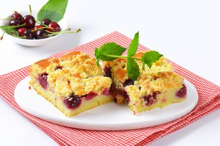 crumb: Sour cherry crumb bars on white wooden serving board