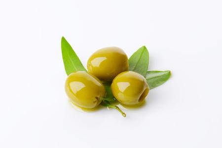 pitted: Tre olive verdi snocciolate con foglie fresche Archivio Fotografico