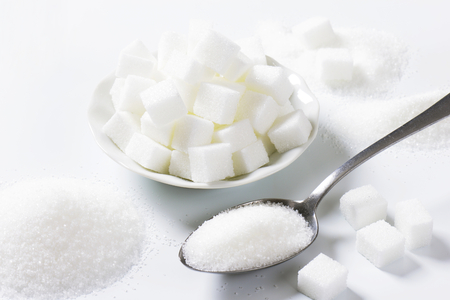 sucrose: Spoonful of fine granulated sugar and pile of sugar cubes