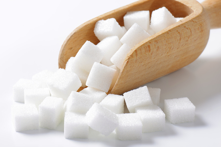 sugar cubes: White sugar cubes in wooden scoop Stock Photo