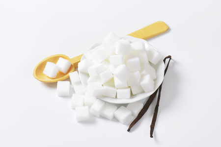 sugar cubes: Pile of white sugar cubes and two dried vanilla beans